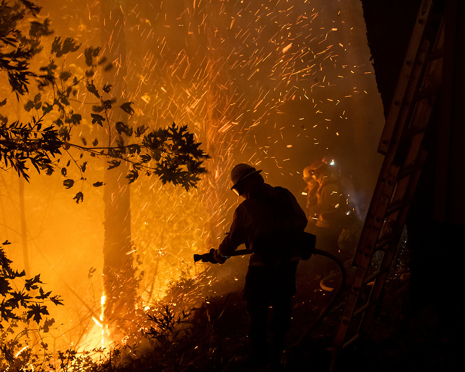 A firefighter sprays water on the Glass Fire on Highway 29 near Calistoga, Calif. on Oct. 1, 2020.