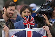 An Asian tv crew interview a royalist during celebrations of the Queen's record of years as monarch.