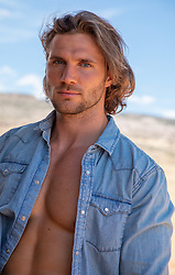 hot man with long brown hair and blue eyes in an open denim shirt