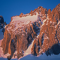14,249′ North Palisade Peak rises above the Palisade Glacier atop the Sierra Nevada Crest in John Muir Wilderness, California.  Starlight Peak, slightly lower, is on the right. The U-Notch Couloir rises to the left and Clyde's Couloir goes up the center.