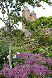 The Rose Garden at Sissinghurst Castle with Allium cristophii syn. A. christophii in the foreground and the Tower beyond