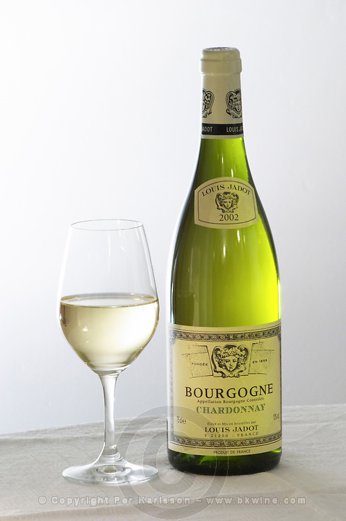 A bottle of Maison Louis Jadot Bourgogne Chardonnay 2002 white burgundy wine and a glass of white wine standing on a table top with a white cloth. Backlit backlight back light lit. white background, Maison Louis Jadot, Beaune Côte Cote d Or Bourgogne Burgundy Burgundian France French Europe European