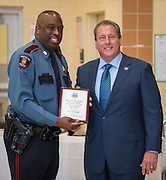 Officer Willie Demby, right, receives the Operations Bureau Campus/Patrol Employee of the Year award from Chief Robert Mock, right, during the Houston ISD Police awards banquet at Thompson Elementary School, August 15, 2014.
