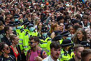 London, United Kingdom, June 27, 2021: Police wearing face protective surgical masks are seen in the middle of thousands of youth people who are attending an anti-government musical rave in central London on Sunday, June 27, 2021. (VX Photo/ Vudi Xhymshiti)