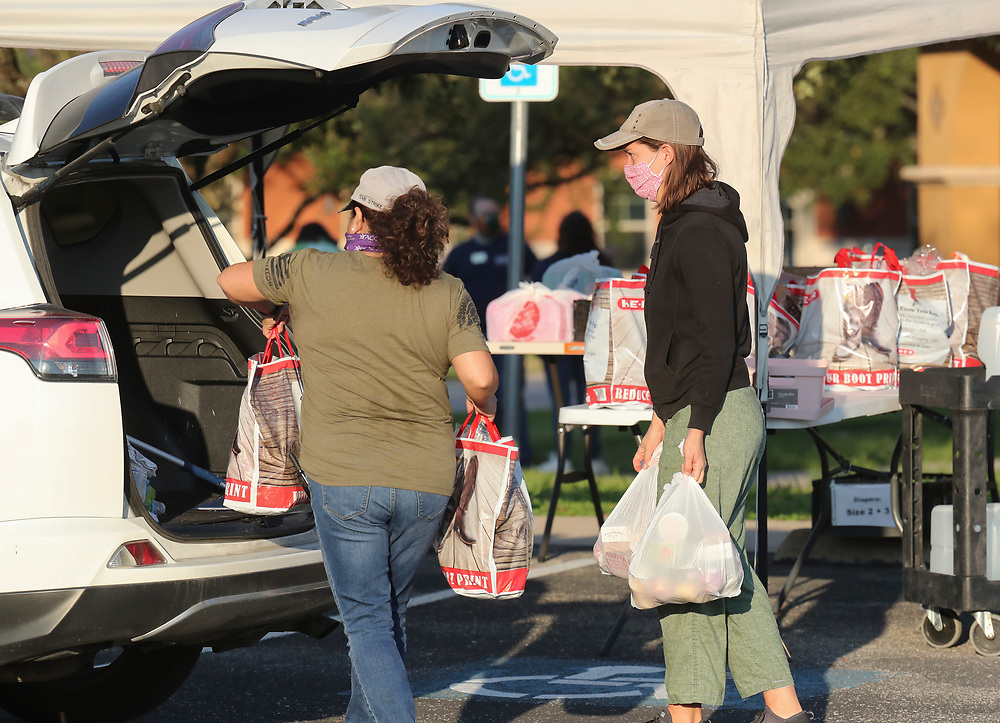 Staff members including Arlene Lozano (l)  help conduct a twice-weekly fresh food drive sponsored by Catholic Charities helping low-income Texans  make ends meet in Austin. The October 1, 2020 effort helped several hundred family members with fruit, meats, milk and cereal.