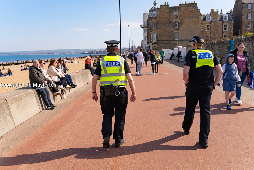 Portobello, Scotland, UK. 16 April 2021. Friday saw Covid-19 travel restrictions lifted meaning the public are free to travel around the country, Sunshine and warm temperatures saw Portobello beach and promenade busy on Saturday afternoon. Police patrols were evident but low key. Iain Masterton/Alamy Live News