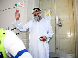 © Licensed to London News Pictures. 19/10/2018. London, UK. Radical preacher ANJEM CHOUDARY is seen waving to media and smiling, outside a bail hostel after being released form Belmarsh Prison in south-east London. Photo credit: Ben Cawthra/LNP