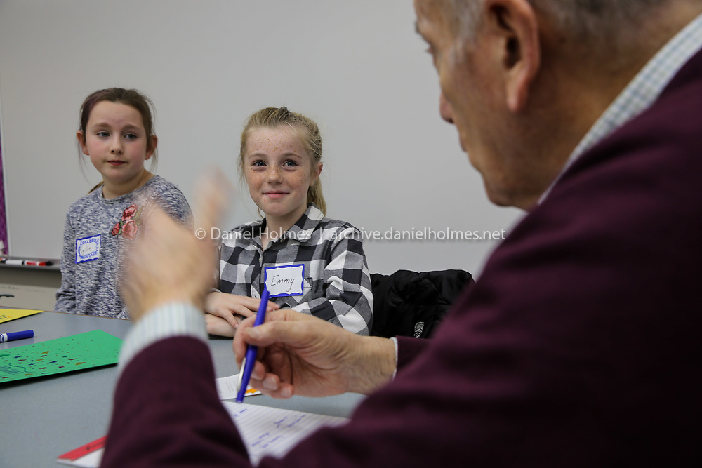 (12/6/18, SUDBURY, MA) Fourth-graders Emmy Acquaviva, center, and Kylie Devoll listen to senior Lee Goodman during a new program that links elementary-grade kids up with senior citizens called Learning Intergenerational Community (LINC), at Noyes Elementary School in Sudbury on Thursday. [Daily News and Wicked Local Photo/Dan Holmes]