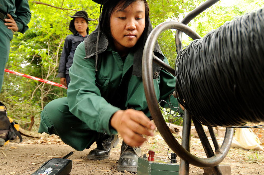 """Female Deputy Team Leader, Phisamai Linsaiyoum, age 20, prepares the last steps connecting the firing device to the black firing wire.  She admitted, """"Just after the large explosion I am very happy because if there is a misfire then I have to go and inspect what is wrong.  At that time it is very dangerous.  But so far I never have a misfire.""""..She detonated 76, BLU 26 cluster bombs, laying buried in the dirt after being located by one of the Mines Advisory Group ladies teams.  She disposed of the bombs without moving them in a controled demolition using TNT and C4 explosives.  It took the team 7 days to clear 14,352 sq meters...Laos was part of a """"Secret War"""", waged within its borders primarily by the USA and North Vietnam.  Many left over weapons supplied by China and Russia continue to kill.  However, between 90 and 270 million fist size cluster bombs were dropped on Laos by the USA, with a failure rate up to 30%.  Millions of live cluster bombs still contaminate large areas of Laos causing death and injury.  The US Military dropped approximately 2 million tons of bombs on Laos making it, per capita, the most heavily bombed country in the world. ..The women of Mines Advisory Group (MAG) work everyday under dangerous conditions removing unexploded ordinance (UXO) from fields and villages...***All photographs of MAG's work must include (either on the photo or right next to it) the credit as follows:  Mine clearance by MAG (Reg. charity)***."""