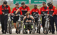 Jon M. Fletcher/Staff - 030803 - With encouraging words from Jacksonville Fire and Rescue Department bike patrollers, Dena Gaylor pumps up the incline of the Hart Bridge near the end of Saturday's Gate River Run 2003.  Gaylor of Valdosta completed the entire 15 K race with a pulled muscle in her arm.