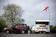 Waiting for customers, a male burger van owner reads the newspaper in his Land Rover, at a layby on the old A45 road on the 26th April 2010 in Felixstowe in the United Kingdom.