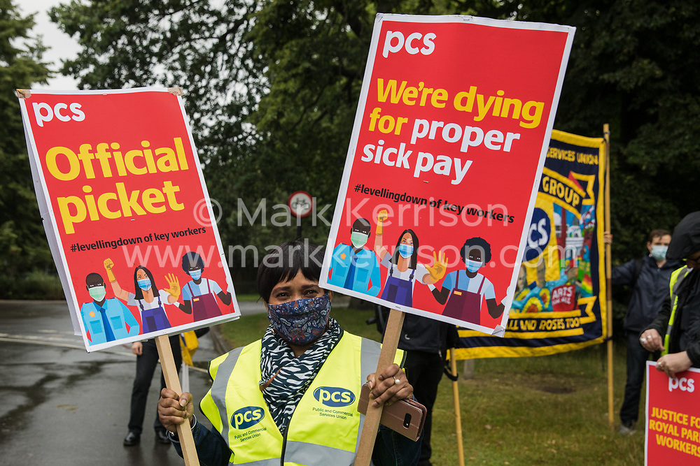 A PCS member holds two placards at a picket outside the Old Police House in Hyde Park for Royal Parks workers outsourced via French multinational VINCI Facilities as part of joint strike action by the United Voices of the World (UVW) and Public and Commercial Services (PCS) trade unions on 30th July 2021 in London, United Kingdom. The joint strike, with members dual carding over pay, conditions and the sacking of a member of staff, is believed to be the first between a TUC and a non-TUC trade union and follows the launch of a legal challenge by the Royal Parks workers against indirect racial discrimination by the Royal Parks.