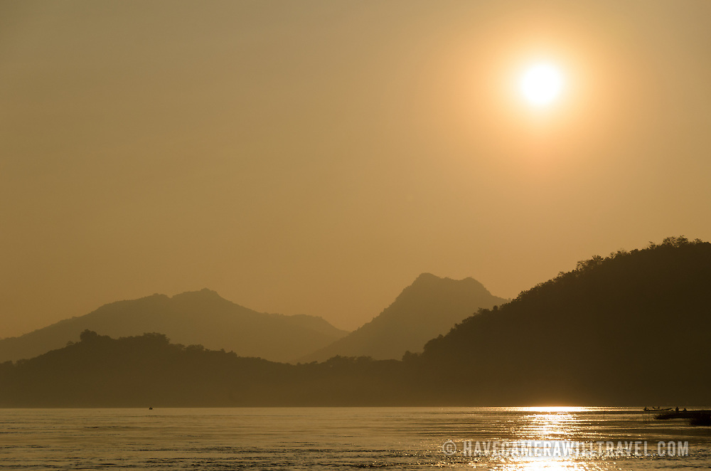 Hills and mountains are silhouetted against the setting sun on the Mekong River near Luang Prabang in central Laos.