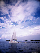 A sailboat drops a smaller dingy into the carribean waters near British Virgin Islands
