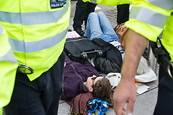 London, UK. 4 September, 2019. Metropolitan Police officers form a cordon around anti-nuclear activists locked together using an arm tube within a shopping basket who they had dragged out of one of the two main access roads to ExCel London during protests on the third day of a week-long carnival of resistance against DSEI, the world's largest arms fair. The third day's protests were organised by the Campaign for Nuclear Disarmament (CND) and Trident Ploughshares.