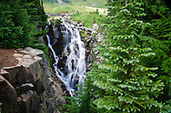 Hikers cross a footbridge above Myrtle Falls on Edith Creek, Paradise Meadows, Mount Rainier NP, WA, USA
