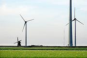 Nederland, Eemshaven, 14-5-2018 In het havengebied in noord groningen staan ruim 90 windturbines waarvan de meesten van RWE. Ook een traditionele ouderwetse klassieke molen, de Goliath, staat in het landschap hetgeen een mooi contrast geeft met de moderne versie. Foto: ANP/ Hollandse Hoogte/ Flip Franssen