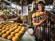 24 NOVEMBER 2015 - BANGKOK, THAILAND:  LEK, a baker in Bang Chak Market, makes the small cakes he sells from his stand in the market. He has been baking and selling cakes in the market for more than 20 years but will return to his home province of Nakhon Si Thammarat when the market closes on Dec 31, 2015. He sells the cakes for about 6Baht ($0.20 US) each. The Bang Chak Market serves the community around Sois 91-97 on Sukhumvit Road in the Bangkok suburbs. About half of the market has been torn down. Bangkok city authorities put up notices in late November that the market would be closed by January 1, 2016 and redevelopment would start shortly after that. Market vendors said condominiums are being built on the land.        PHOTO BY JACK KURTZ