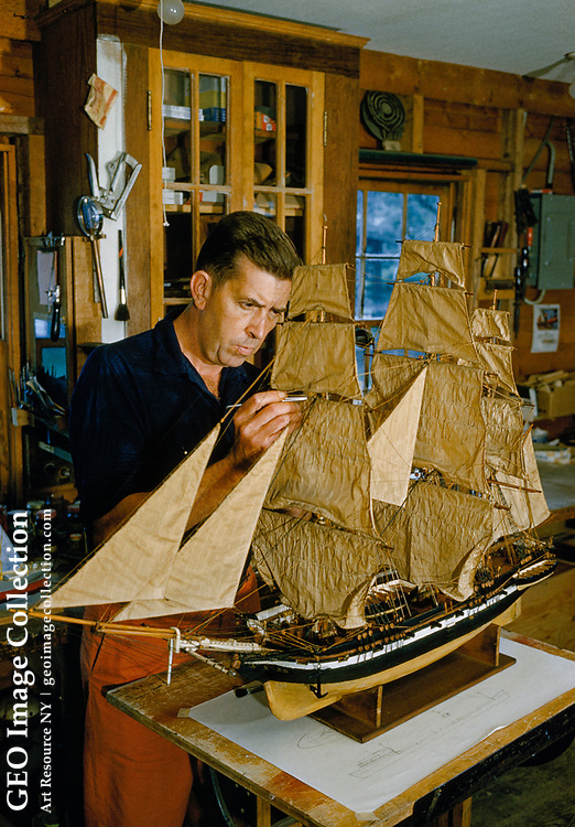 An man repairs rigging on a model of the Decatur, an 1839 sloop-of-war