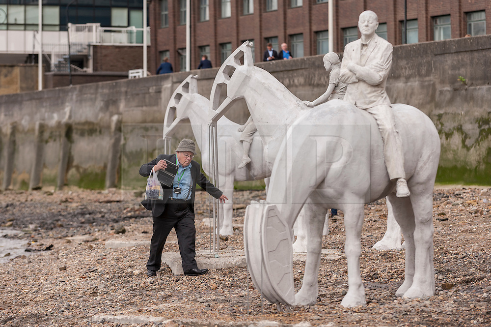 """© Licensed to London News Pictures. 02/09/2015 London, UK. A man walks amongst the art installation entitled """"The Rising Tide"""" (comprising four horse-riders on horses with petroleum pumps for heads) by the underwater eco-sculptor Jason deCaires Taylor, which stands on the foreshore of the River Thames in Vauxhall and is revealed with each low tide.  The installation aims to question man's reliance on fossil fuels and is part of this year's Totally Thames festival. Photo credit : Stephen Chung/LNP"""