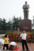 Visitors kowtow to a statue of Mao Zedong at the Statue Square near Mao's birthplace in Shaoshan, Hunan Province, China on 12 August 2009.  The village of Shaoshan, in rural Hunan Province, is tiny in size but big in name. It was the childhood home for Mao Zedong, the controversial revolutionary who came from obscurity but eventually defied all odds conquered China in the name of communism. Now his home, a sacred place among China's official propaganda, is in reality a microcosm of the country itself: part commercialism, part superstition, with a dash of communist ideological flavor.