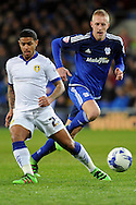 Leeds United's Liam Bridcutt (l) plays the ball while challenged by Cardiff City's Lex Immers. Skybet football league championship match, Cardiff city v Leeds Utd at the Cardiff city stadium in Cardiff, South Wales on Tuesday 8th March 2016.<br /> pic by Carl Robertson, Andrew Orchard sports photography.