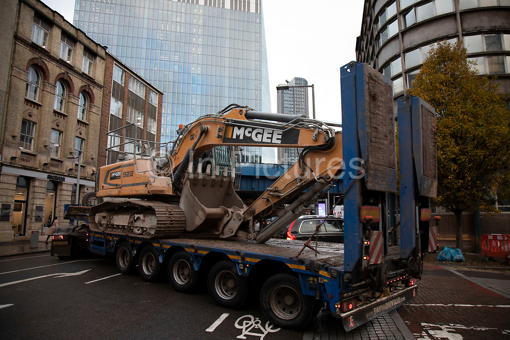 Large low loader heavy goods vehicle carrying a McGee digger turning right onto Southwark Street on 27th November 2019 in London, England, United Kingdom. A great deal of construction in the capital means that the roads are often full of heavy good vehicles, which is a road safety concern for many other road users.