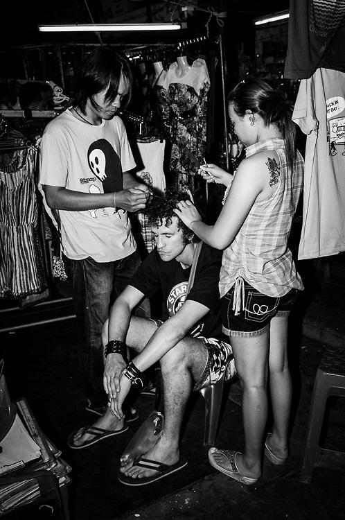 A traveler gets his hair done on Khao San Road in Bangkok, Thailand (November 19, 2011)