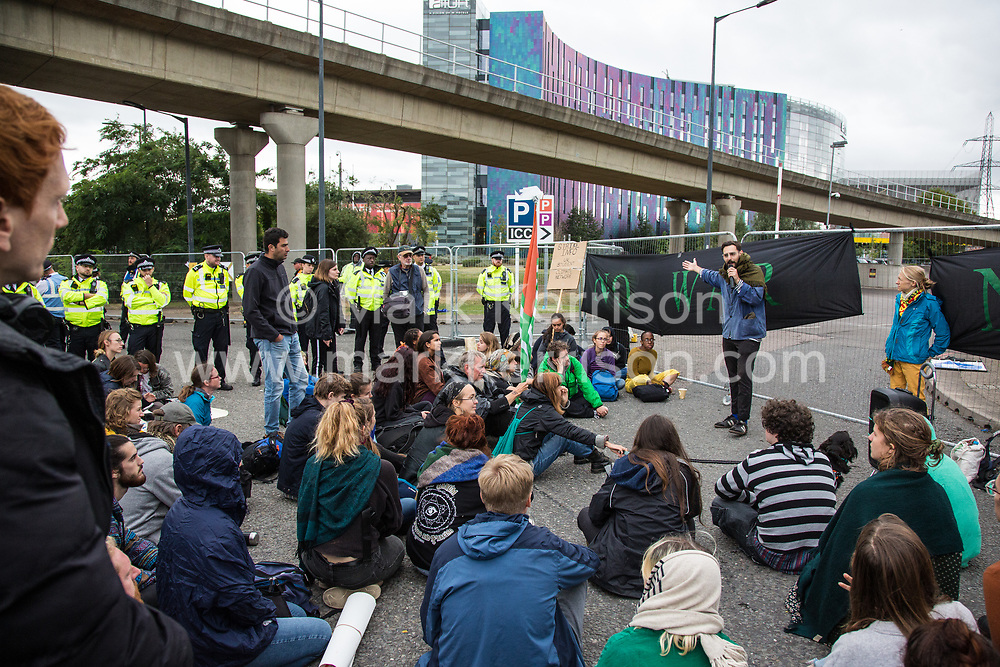 London, UK. 6 September, 2019. Climate activists block an access road during Stop The Arms Fair protests outside ExCel London on the fifth day of a week-long carnival of resistance against DSEI, the world's largest arms fair. The road remained blocked for several hours. The fifth day of protests was themed as Stop The Arms Fair: Stop Climate Change in order to highlight links between the fossil fuel and arms industries.