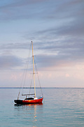 A peaceful sunrise scene of a red sailboat on Kailua Bay on the island of Oahu, Hawaii.