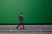 Street Scene of people passing by a green painted wall on in Soho, London, England, United Kingdom. The simplicity of the scene helps highlight the figures of ordinary people going about their daily lives. Woman with headphones and bags.