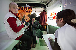 MSF nurse Ania Sharaya (l) and Doctor Victoria Pogorelova consult with a patient in the MSF mobile clinic van in a neighbourhood of Debaltsevo.