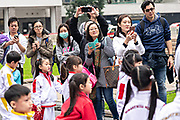 Hong Kong Chinese parents watch and photograph their children rehearse cheerleading routines at Statue Square in Central District, Hong Kong.
