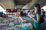 A walk along the Southbank in London. Chinese woman stands engrossed reading a Roald Dahl book at the second hand book stalls under Waterloo Bridge. Every day the books are laid out on these tables and in the evening the light illuminates them.This area is very popular especially on the weekends for Londoners to walk and see different arts, culture and entertainment.