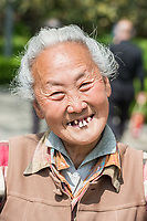 Shanghai, China - April 7, 2013: old chinese woman friendly toothless toothy smiling outddors portrait at the city of Shanghai in China on april 7th, 2013