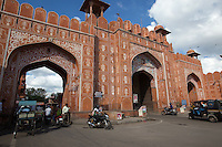 """Ajmeri Gate is one they arched entrances into the walled """"Pink City"""" of Jaipur. The gate is finely decorated with floral motifs with mythological figures above the central door. The walls were built by Maharaja Jai Singh when Jaipur was first founded as India's first planned cities."""