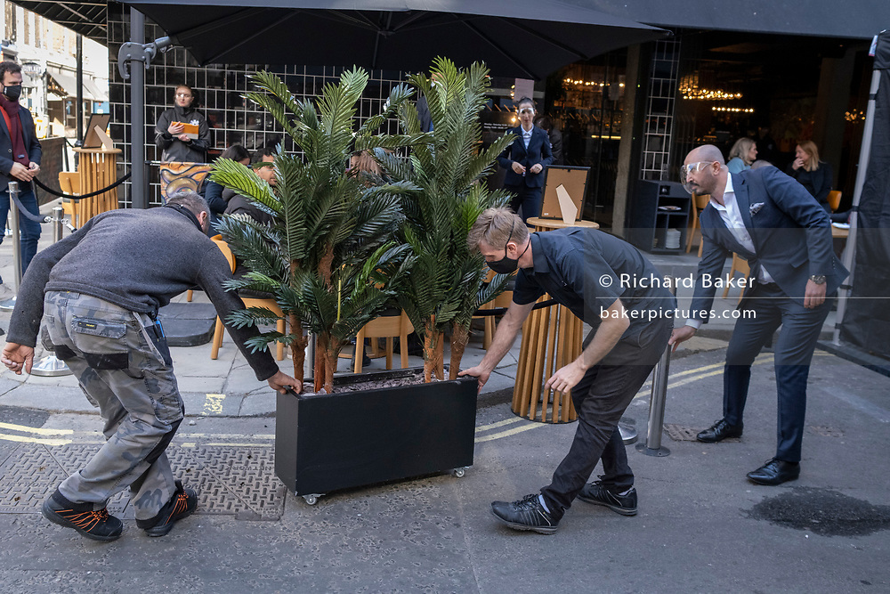 On the day that the UK government eased Covid restrictions to allow non-essential businesses such as shops, pubs, bars, gyms and hairdressers to re-open, bar staff position potted plants outside their business on Frith Street in Soho, on 12th April 2021, in London, England.