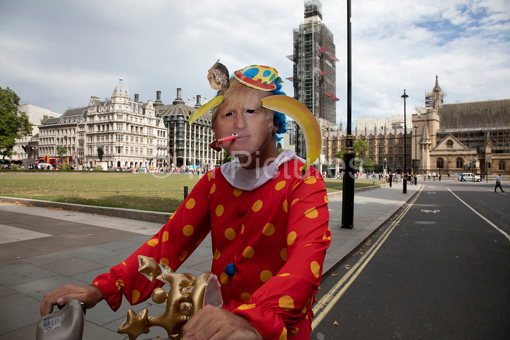 Anti Brexit protester dressed up as a clown version of Prime Minister Boris Johnson hires a Boris bike in Westminster as it is announced that Boris Johnson has had his request to suspend Parliament approved by the Queen on 28th August 2019 in London, England, United Kingdom. The announcement of a suspension of Parliament for approximately five weeks ahead of Brexit has enraged Remain supporters who suggest this is a sinister plan to stop the debate concerning a potential No Deal.