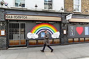 A man walks beside a graffiti which is a sign of support for the NHS (National Health Service) in Soho near Leicester Square in central London on Monday, May 11, 2020. <br />