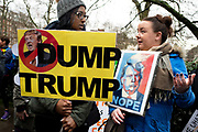 Stop Trump's Muslim ban demonstration on 4th February 2017 in Grosvenor Square, London, United Kingdom. The protest was called on by Stop the War Coalition, Stand Up to Racism, Muslim Association of Britain, Muslim Engagement and Development, the Muslim Council of Britain, CND and Friends of Al-Aqsa. Thousands of demonstrators gathered to demonstrate against Trumps ban on Muslims, saying it must be opposed by all who are against racism and support basic human rights, and for Theresa May not to collude with him. Ayoung black woman holds a placard saying Dump Trump and stands next to a woman with one with an image of Trump and the words Nope.