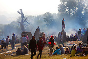 Smoking fires from the short summer night are still smouldering the morning after in the stone circle, Glastonbury Festival 2010