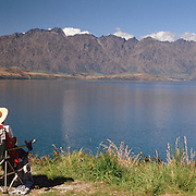 An elderly couple watch the TSS Earnslaw cruise past The Remarkables Mountain Range, Queenstown, New Zealand. The TSS Earnslaw, a 1912 Edwardian vintage twin screw steamer on the waters of Lake Wakatipu, Queenstown, New Zealand. It is one of the oldest tourist attractions in Central Otago, and the only remaining passenger-carrying coal-fired steamship in the southern hemisphere. The TSS Earnslaw heads along Lake Wakatipu from Queenstown daily, running tourist trips to Walter Peak Station passing magnificent peaks and contrasting shoreline foliage along the lakeside. Queenstown, New Zealand.  Photo Tim Clayton