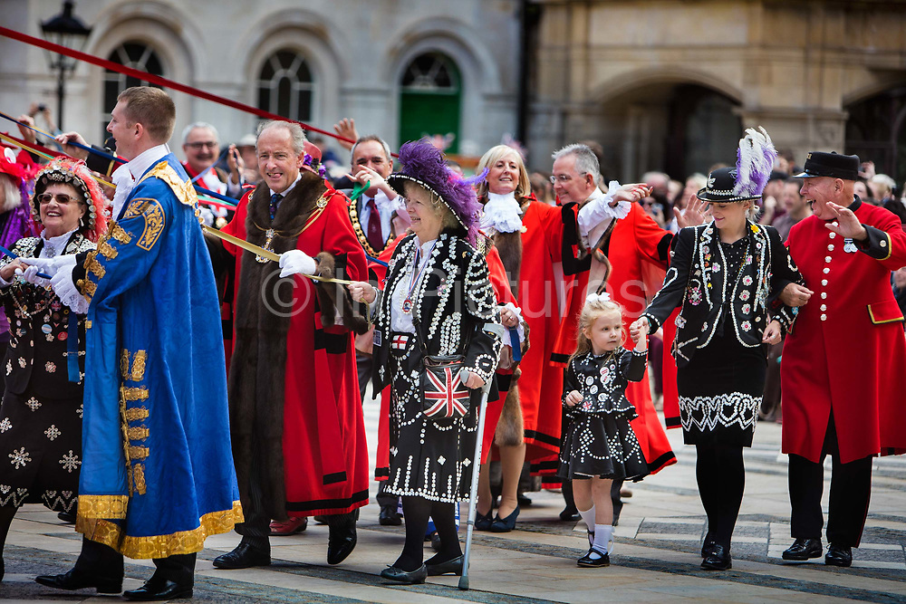 Pearly Kings and Queens are joined by Chelsea pensioners and the mayors of Londons boroughs for the Harvest Festival celebrations at Guildhall Yard. The annual event features early English entertainment including maypole dancing, Morris dancers and a marching band. The London tradition of the Pearly Kings and Queens began in 1875, by Henry Croft. Inspired by the local Costermongers, a close-knit group of market traders who looked after one another and were recognisable by buttons sewed onto their garments, Henry went out on the streets to collect money for charity, wearing a suit covered in pearl buttons to attract attention. When demand for his help became too much, Henry asked the Costermongers for assistance, many of whom became the first Pearly Families. Today, around 30 Pearly Families continue the tradition to raise money for various charities.