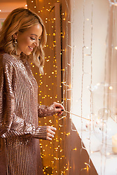 Woman Lighting Candle by Window Smiling