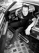"Joe Strummer poses in vintage Lincoln outside Epitaph Records following the release of the Mescaleros ""Rock Art and the X-Ray Style"""