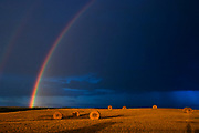 bales and raibow with storm clouds<br />Cypress River<br />Manitoba<br />Canada