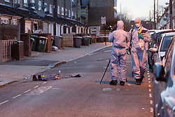 © Licensed to London News Pictures. 25/03/2016. London, UK. Forensic officers photograph personal effects in the road within the police cordon in Tower Hamlets Road, behind Magpie Close in Forest Gate, east London. Five people have been taken to hospital, with one man in a critical condition. Photo credit : Vickie Flores/LNP