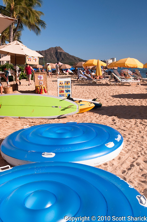 Beach floats and umbrellas along Waikiki Beach with the peak of Diamond Head showing in the distance.
