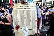 A protester hold a list of victims of racist attacks as people take part in a memorial demonstration to the victims of the Hanau terror attack, in Berlin, Germany, August 19, 2020. Thousands of protesters marched through the German capital's Neuköln district in remembrance of the Hanau shootings, in which ten people were killed and five others wounded. The shooting spree was committed on February 19, 2020 by a far-right extremist targeting two shisha bars and kiosks at the Hessian city of Hanau near Frankfurt. The gunman was identified as 43-year-old Tobias Rathjen. The majority of the victims were Germans with migrant backgrounds, among the victims was also the perpetrator's mother. (Photo by Omer Messinger)