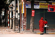 Burma/Myanmar, Mandalay. monks waiting for food donations on the street of Mandalay.